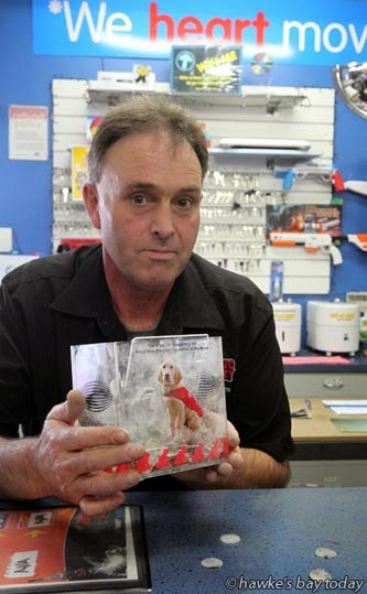 Kevin Knox, owner, Video Ezy Greenmeadows, Napier, with a charity donation box for Royal New Zealand Foundation for the Blind, which a Video Ezy member tried to steal, but was thwarted by the Velcro dots by which it was attached to the counter. photograph