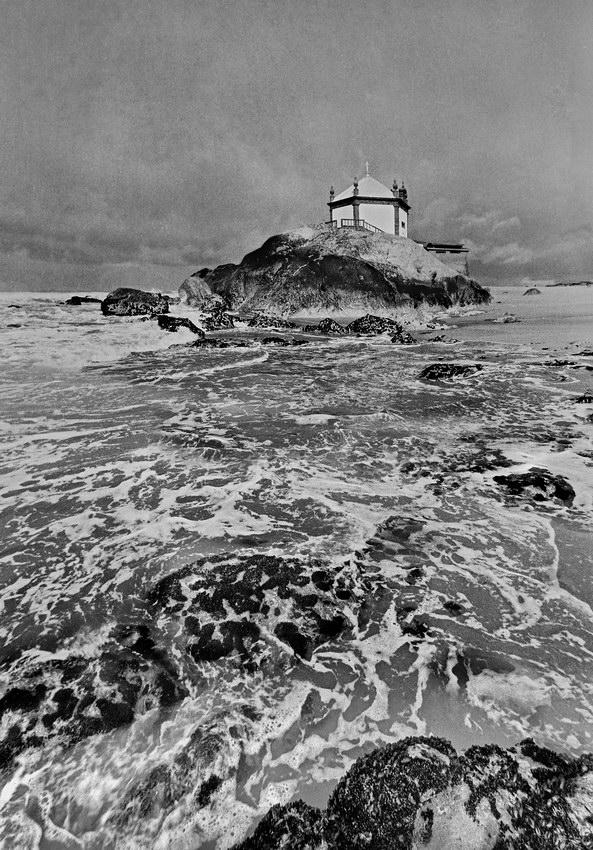 Fotografia com fime a preto e branco com o espraiar da onda em primeiro plano, muito prolongado e a capela ao fundo quase toda rodeada de água. Céu nublado