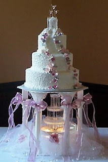 Three Tier Pink And White Castle Wedding Cake Raised Up On 5 Pillars To Allow A Fountain Underneath The Is Decorated With Long