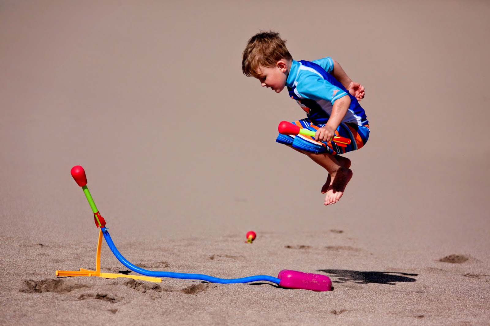 A little boy jumping to land on a toy rocket launcher at Sand Danes National Park.