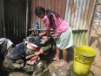 Mujer lavando en una piedra, pobreza