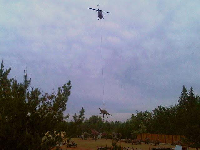 dinosaurios siendo transportados en helicoptero