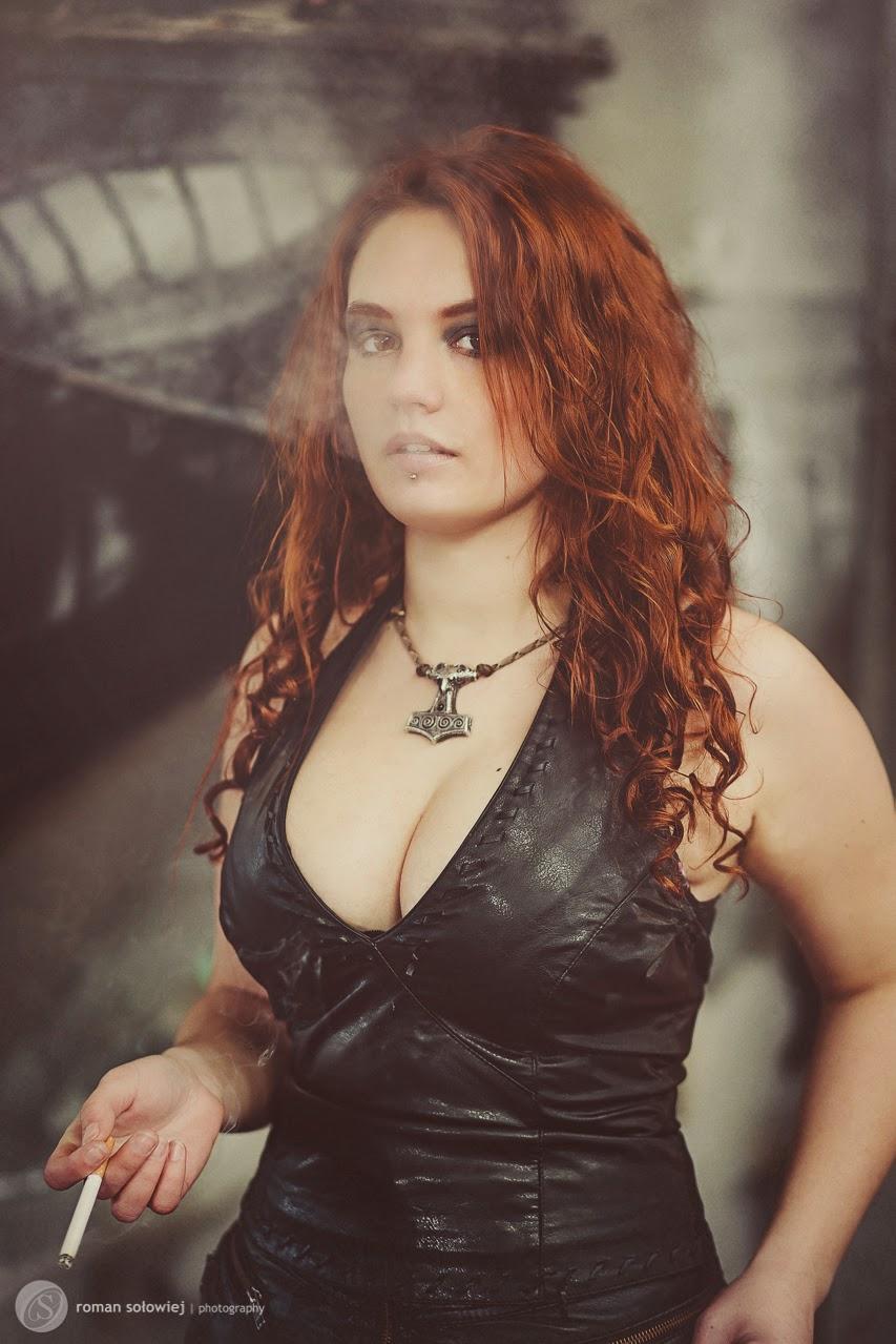 superbe jeune femme rousse en bustier de cuir décolleté et fumant une cigarette