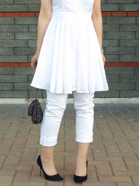 styling a white dress over white skinny jeans, with black pumps and accessories