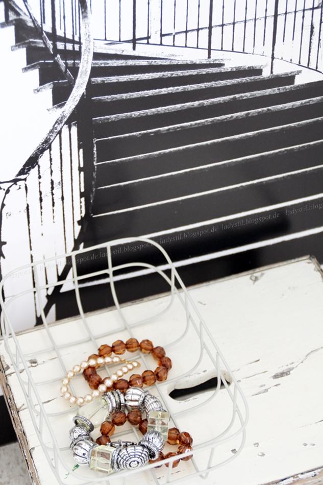 Treppenbild in Schwarz weiß davor ein kleiner Hocker mit Drahtkorb