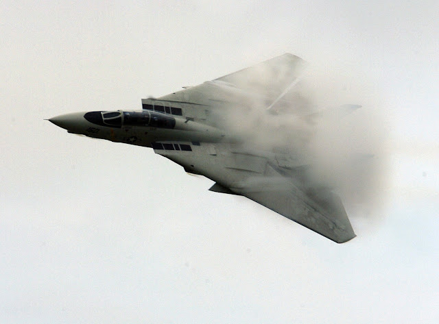 F-14D in a high-speed flyby causing vapor to form