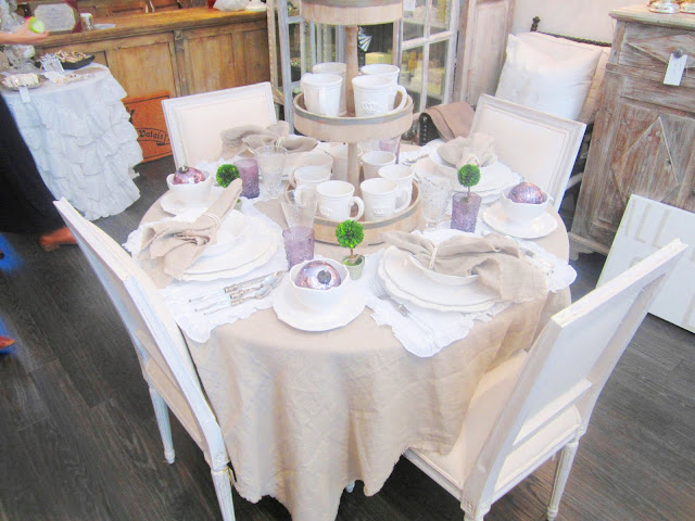 Pom Pom table setting with  linen napkins and table clothes and lavender glasses