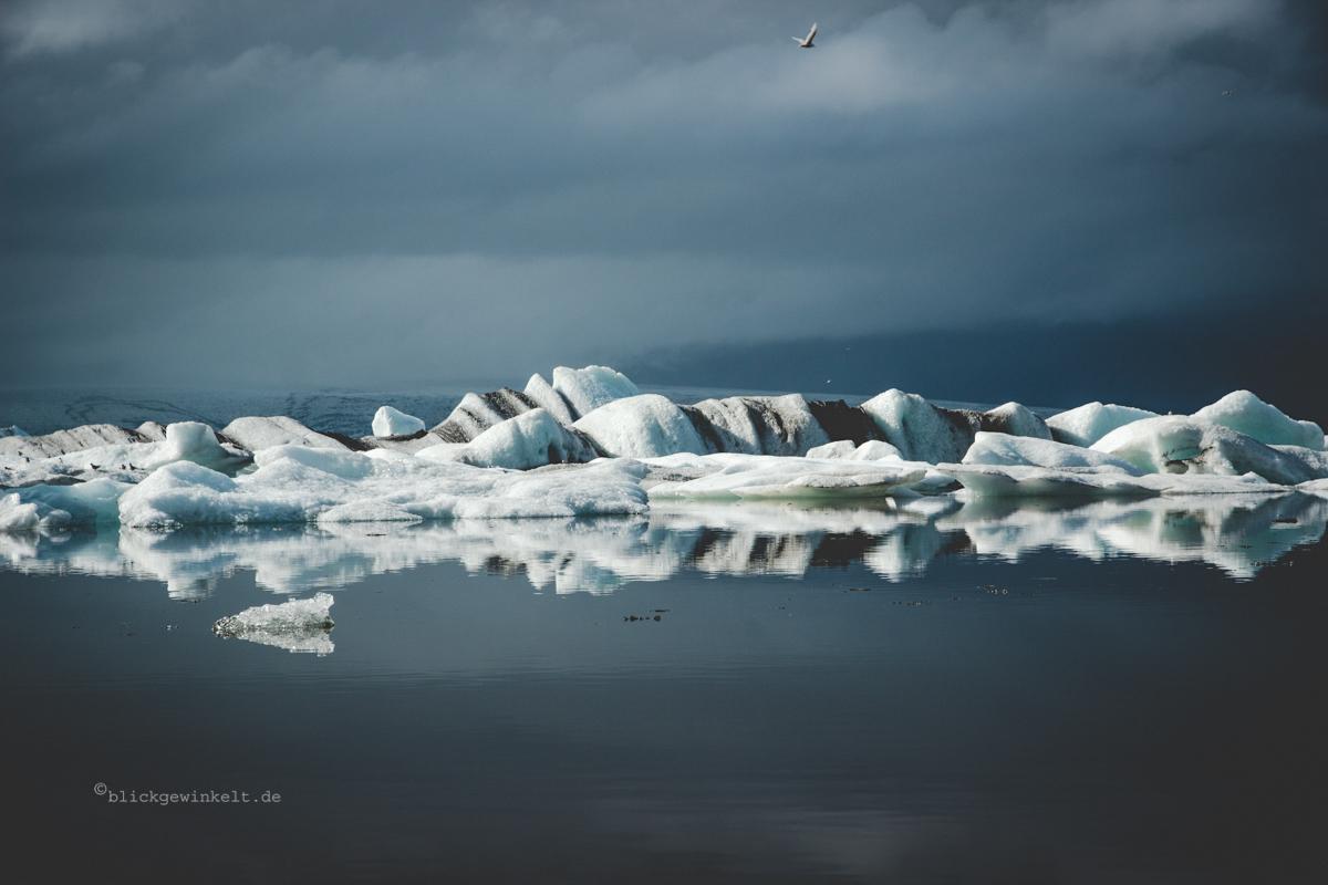 Weiße Eisberge vor dramatisch grauem Himmel