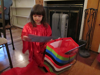 Curly opening a gift in a striped bag, and taking out a pack of stickers