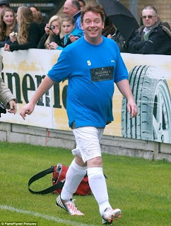 Eastenders' Adam Woodyatt wearing football kit and looking smiley