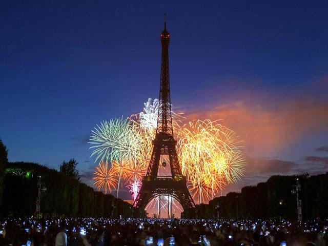 Torre Eiffel à noite em meio a fogos de artifício.