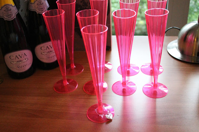 pink plastic champagne flutes with bride champagne glass charm and champagne in background
