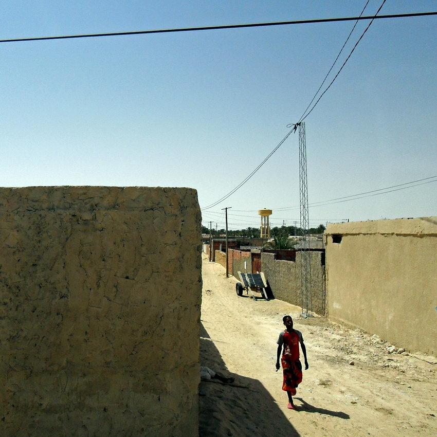 Foto de uma rua em terra com um rapaz a caminhar. Postes e cabos de electricidade na imagem. À esquerda, uma parede vazia preenche grande parte do espaço