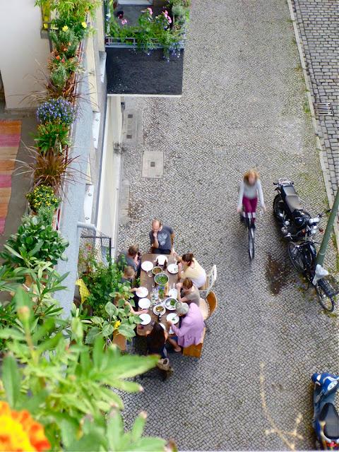 Vor dem zur Galerie umgebauten Ladengeschäft eines Nachbarn steht der Abendessenstisch, an dem viele Leute sitzen. Rechts am Gehwegrand parken zwei Motor- und ein Fahrrad, eine Fahrradfahrerin fährt vorbei. Und links an der alten, zum Teil stark ausgewaschenen Fassade, viele, viele Balkonblumen ...