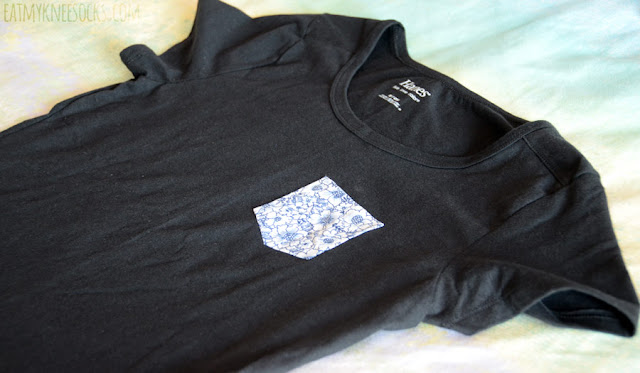 The Blue Hibiscus pocket tee from Tea Apparel features a cute floral printed pocket design on a simple, casual short-sleeve black T-shirt.