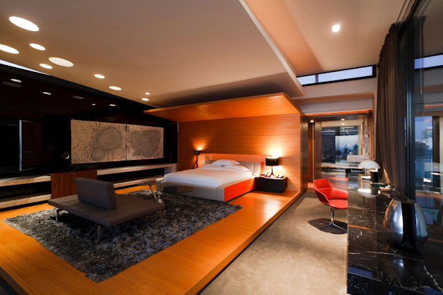 Picture of modern bedroom interiors with the bed in the wooden pedestal along with the grey carpet and small sofa