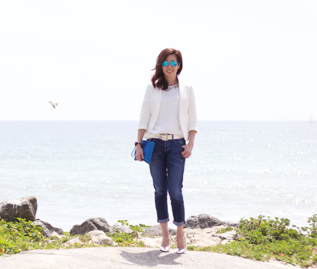 full length image of outfit featuring white jacket, boyfriend jeans, silver belt