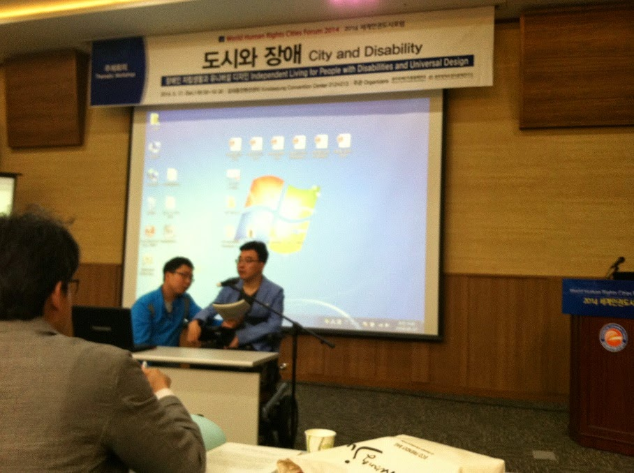 man in wheelchair giving presentation.  Desk in front of him, screen behind him.  Man to his right holding paper as accommodation