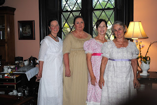 four of my guests standing in front of a large window in the parlor dressed in period dresses from the early 1800s in light colors