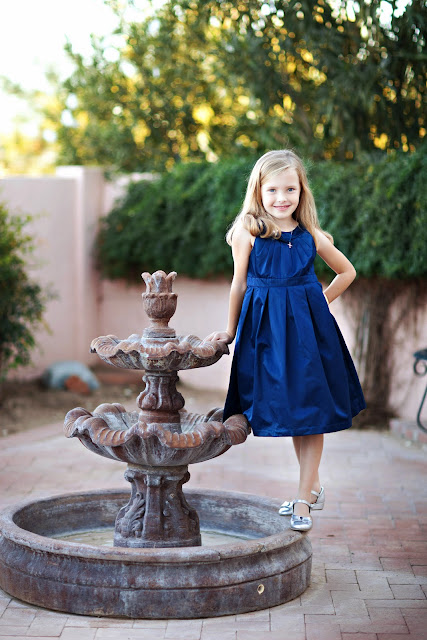Tucson child balances on fountain wearing blue party dress and simple accessories