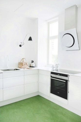 White kitchen with black appliances and green linoleum tile floor
