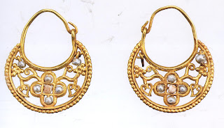 These earrings represent a style that was very popular during the early Byzantine and Islamic worlds. The flower motif with vines, leaves, and clusters of grapes are cut from sheet gold in a delicate open-work design. The centers of the flowers are made up of small pearls.