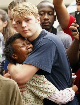Una mujer negra y un hombre blanco lamentan el fallecimiento de Mandela