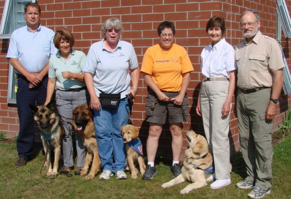 Six people pose outside in front of a brick building on grass. From left to right, a man wearing a light blue shirt and blue pants with his hands folded at his waist, a short woman with short brown hair wearing a light green shirt and khaki pants has two german shepherds on either side of her, a woman with white hair and glasses wearing a light blue shirt and blue jeans with a black bag at her waits has a small golden retriever puppy on her left side. The puppy is sitting and is wearing a blue bandana. A short brown haired woman with glasses wearing an orange t-shirt and dark khaki shorts is holding a brown leash in her hands at her waist. A golden retriever is lying on the ground to her left and is looking up at her. A short brown haired woman wearing a white shirt and khaki pants is standing next to a man with a gray beard and glasses, he is wearing a tan shirt and green khaki pants. It is very sunny and everyone is almost squinting with the sun in their eyes.