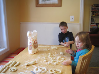 Children rolling dough into pretzel shapes