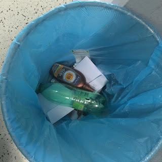 aurinkorasvapullo roskiksessa