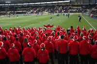 The choir, all dressed in red, stand on the pitch