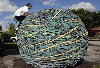 Joel Waul, 28, climbs on top of his rubber band ball outside his home in Lauderhill, Fla