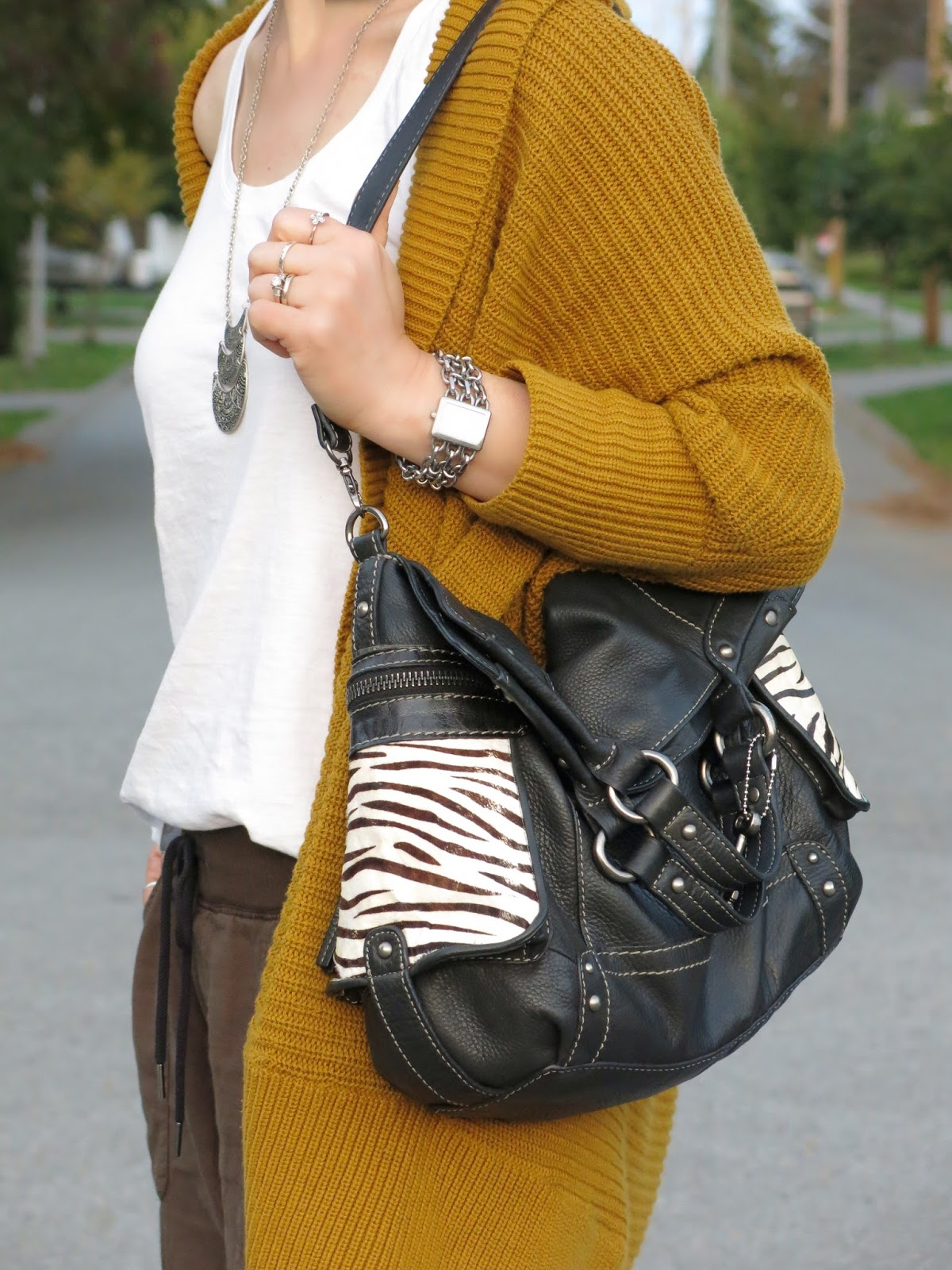 drapey mustard-yellow cardigan, white tank, and zebra-striped Fossil bag