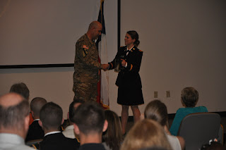 A cadet makes a presentation to a commander.
