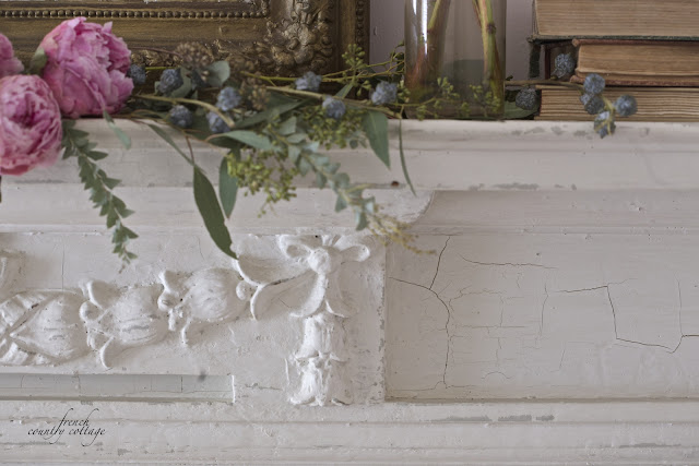 Antique fireplace mantel with peonies and greens