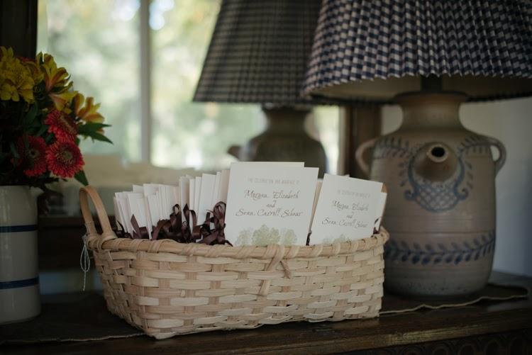 wedding program in a wicker basket on antique dresser with lamp