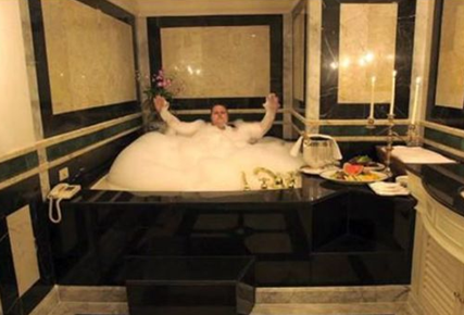 kim dotcom sitting in his giant bathtub in his new zealand mansion