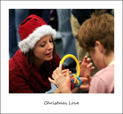 woman in Santa hat interacting with child