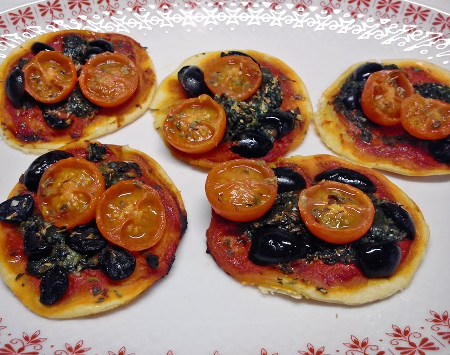 Pizzetas de espinacas, tomatitos y aceitunas.