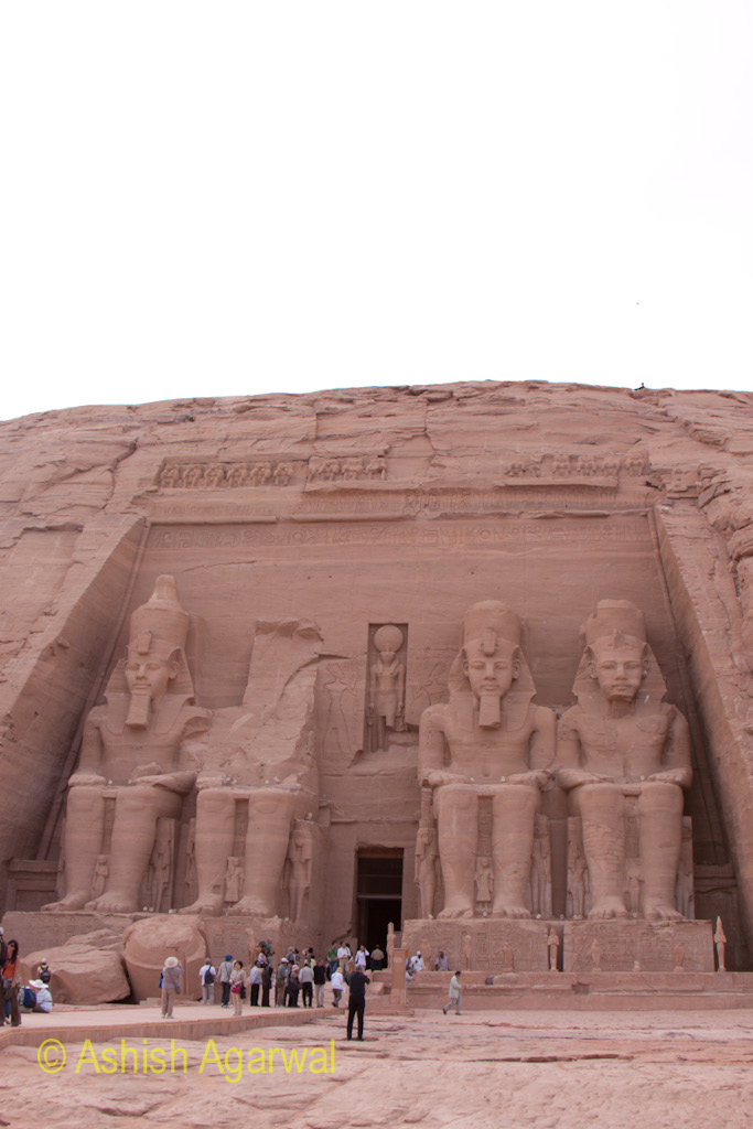 Tourists standing at the foot of the huge statues at the Abu Simbel temple in Egypt