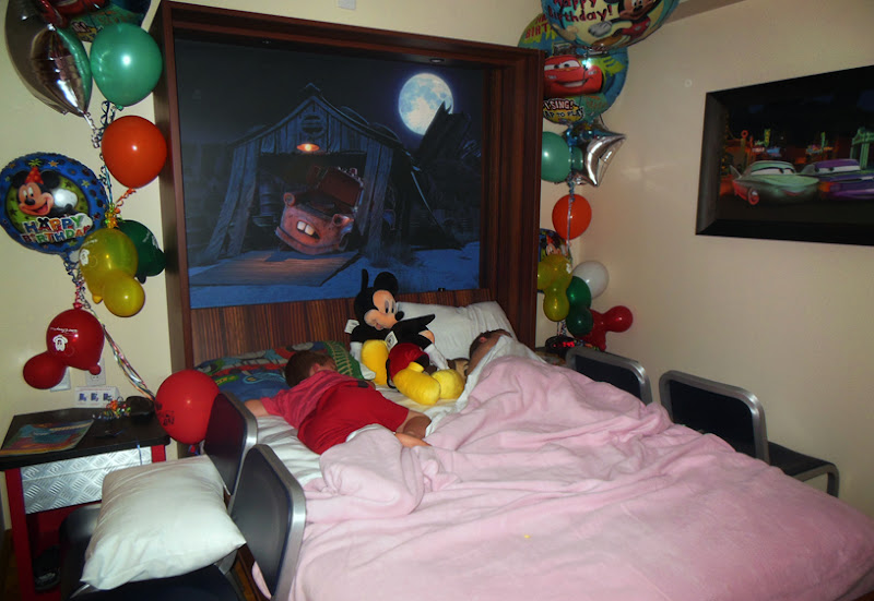 This is the bed pulled down and the boys snuggled down for the night.  The picture of Mater above their heads was complete with a built in night light in the form of the moon and the light above Mater on the barn.  A dimmer switch controlled how bright the lights in the picture got.  Seriously?  Genius again.