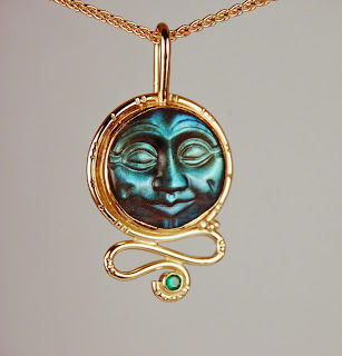 18k yellow gold pendant with carved moon face and emerald