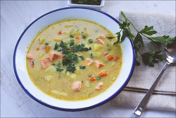 Schnelle Suppe zum Feierabend mit Kartoffeln, Erbsen, Lachs und Kokosmilch, mit Petersilie auf einem Suppenteller serviert
