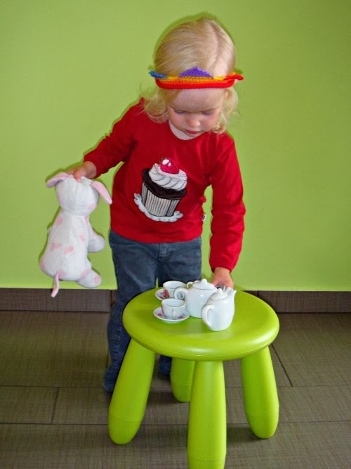 child having a tea party with her toy dog