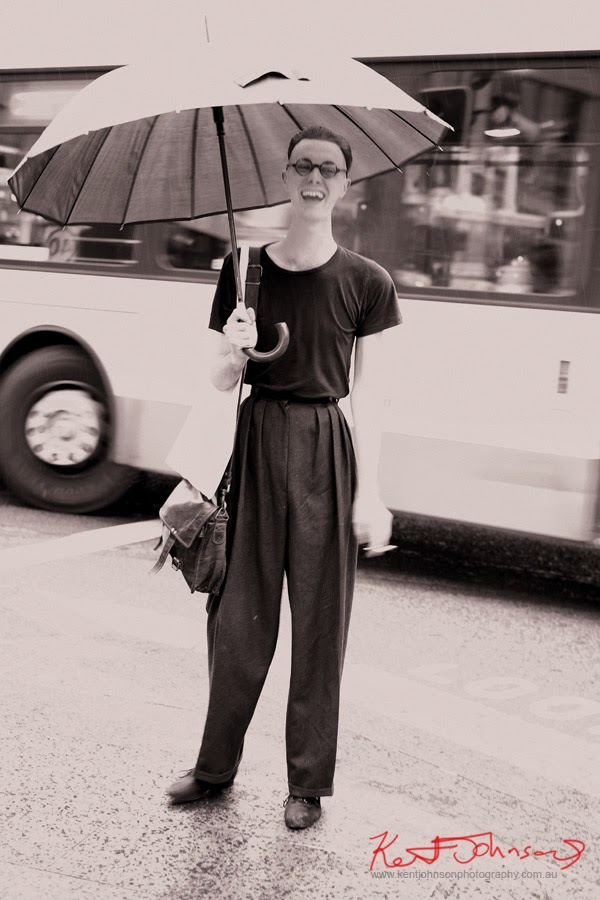 men's fashion, personal style - large black umbrella, Grey flannel trousers, black Tee shirt, leather satchel and the round heavy spectacle frames