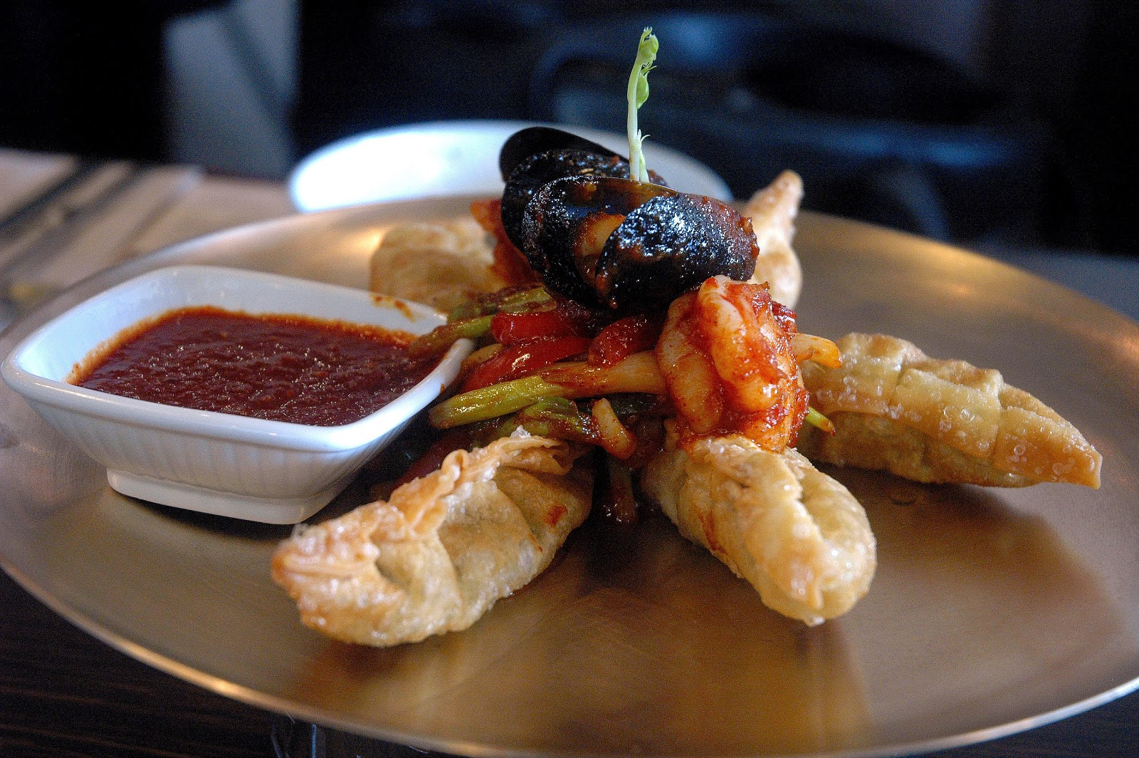 dumplings topped with spicy mussels, shrimp, squid and a spicy dip