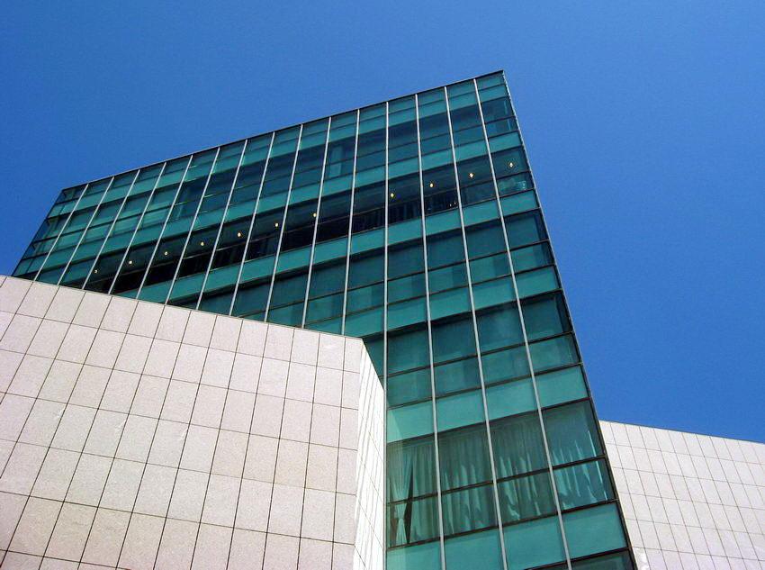 Foto do edifício mais alto, com revestimento em vidro, ladeado por dois mais baixos, revertidos com ladrilhos