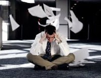Man sitting on floor, head in hands, with paper swirling around