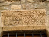 Inscripció en francès i espanyol en la llinda d'una finestra de la façana de Can Xarina