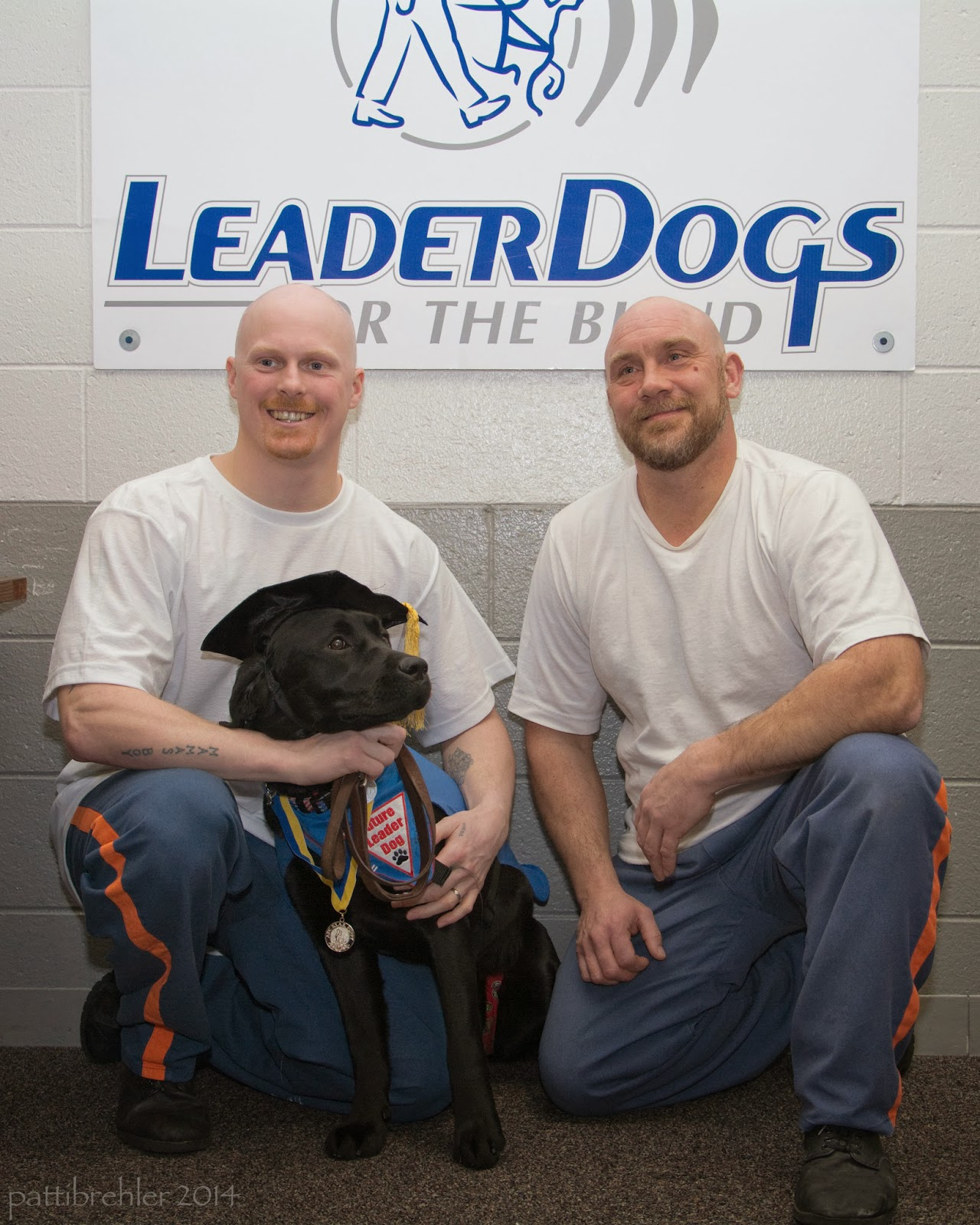 Two men are kneeling on one leg with a black lab sitting in front of the man on the left. That man is holding the dog with his hands. The men are wearing white t-shirts and blue pants with orange strips. Both men have shaved heads. The lab is wearing a black graduation cap with a yellow and lube ribbon around its neck with a medal and a blue bandana. A white poster is on the wall behind them that says Leader Dogs for the Blind.